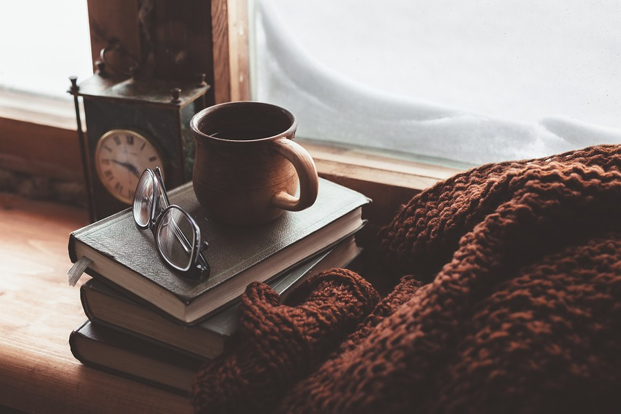 Warm and comfy winter concept. Book, cup of tea and sweater on wooden window sill in old house. Read