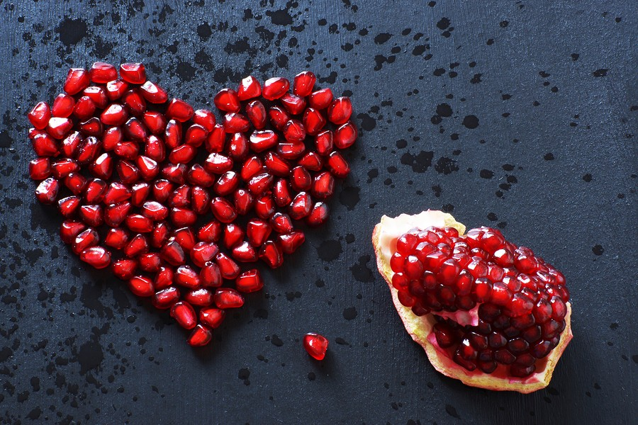 Pomegranate Seeds Are Stacked In The Form Of A Heart On A Black Background, Sprinkled With Water, Ne
