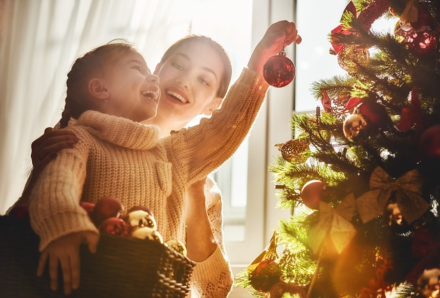 Merry Christmas and Happy Holidays! Mom and daughter decorate the Christmas tree indoors. The mornin