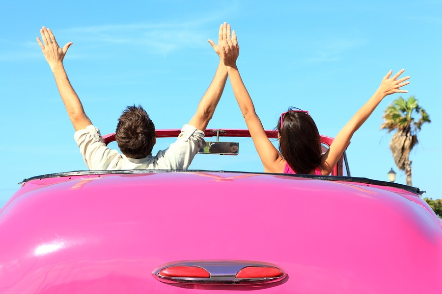 Freedom - happy free couple in car driving in pink vintage retro car cheering joyful with arms raise