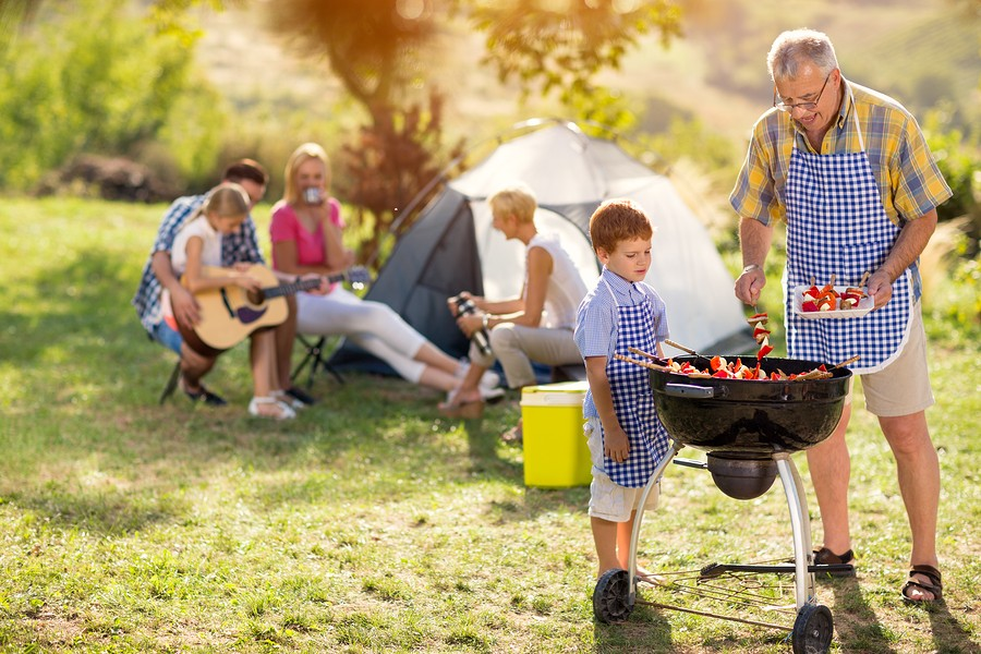 Generation family cooking on grill on camping