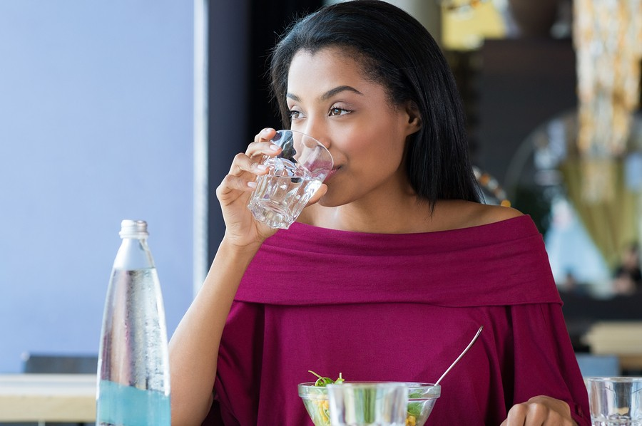 Closeup shot of young woman drinking a glass of water. African girl drinking water durinh her lunch