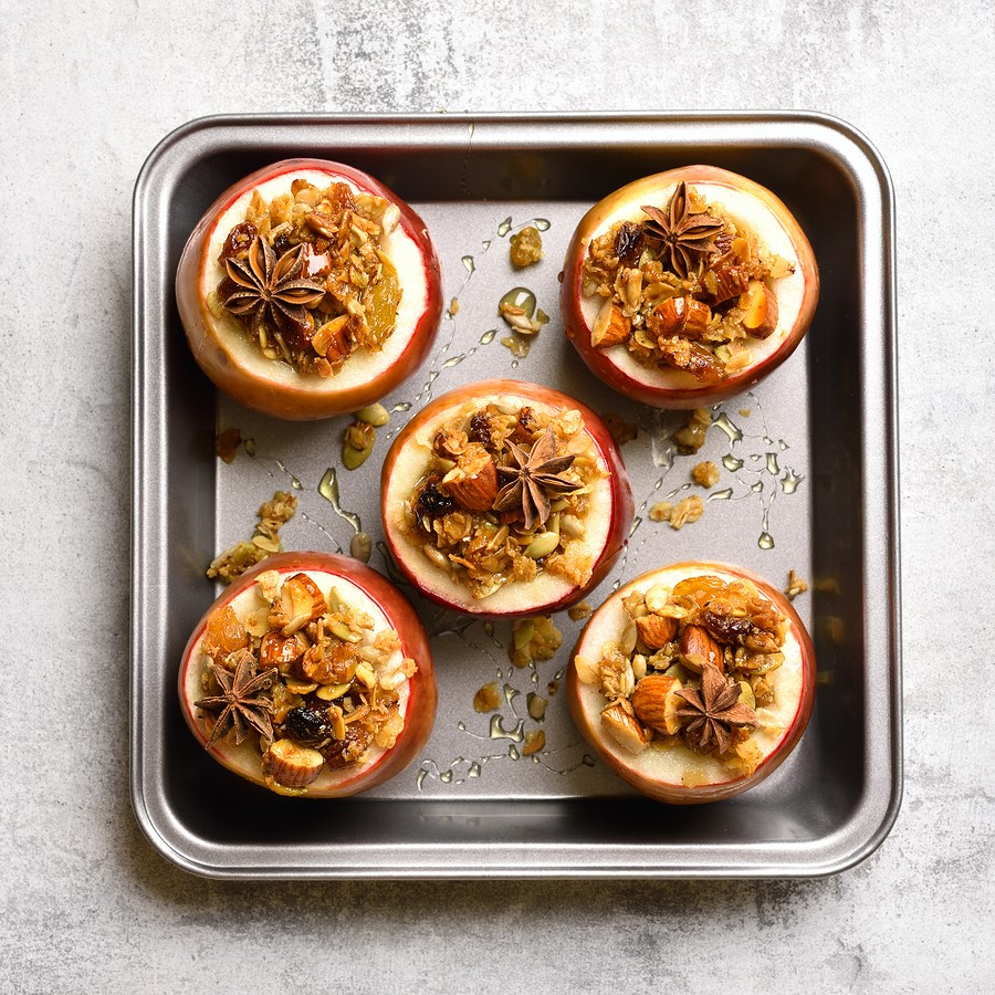 Red Baked Apples With Granola, Cinnamon, Nuts And Honey On Stone Background. Healthy Fruit Dessert.