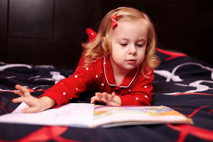 Cute Girl Reading A Book On The Bed