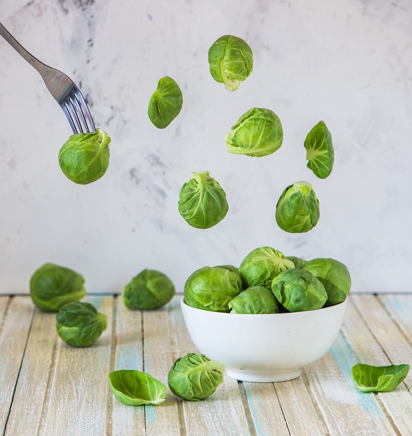 Brussels Sprouts Flying Over A Bowl. Fresh Brussels Sprouts. Levitation Concept