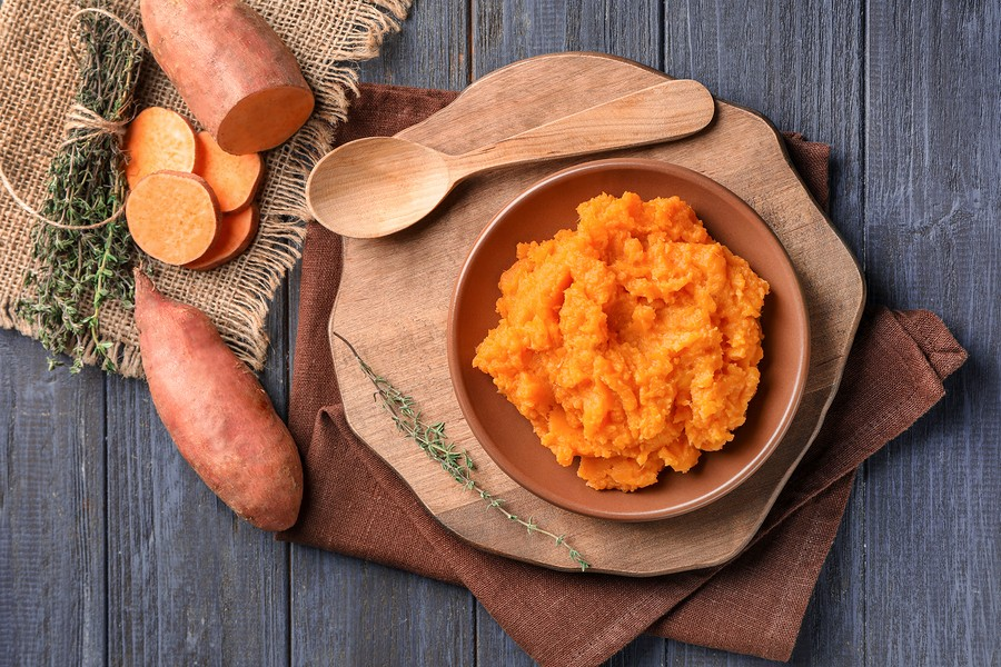 Composition with mashed sweet potato on wooden background
