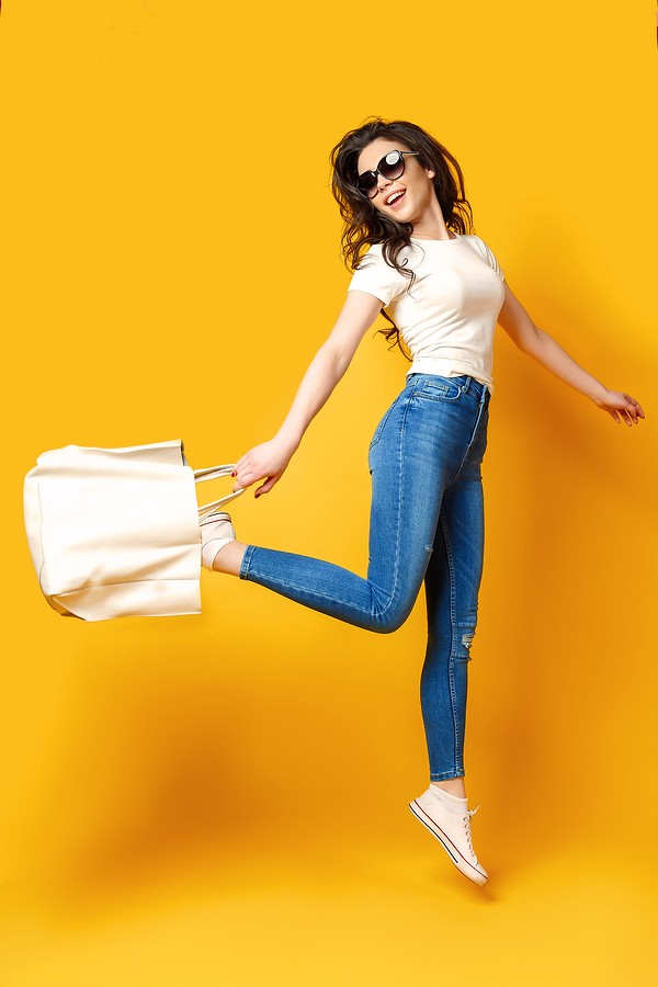 Beautiful Young Woman In Sunglasses, White Shirt, Blue Jeans Posing, Jumping With Bag On The Yellow