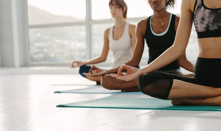 Cropped Shot Of Fitness Women Practising Yoga, Sitting On Floor With Legs Crossed And Hands On Knees