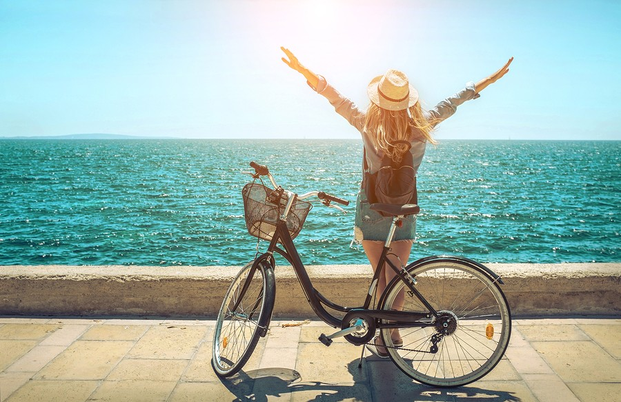Blonde woman in summer hat with her bicycle walking coastline by the sea beach. Sea view. Freedom. W