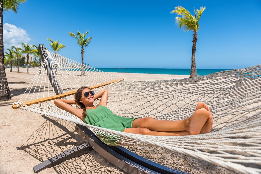 Happy girl relaxing on beach hammock in tropical vacation resort hotel. Holidays in the Caribbean ta
