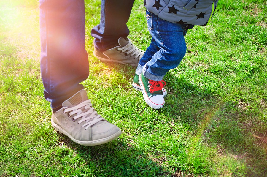 First Steps Concept - Foot Of Father And Son In Stylish Sneakers On The Background Of Green Grass. B