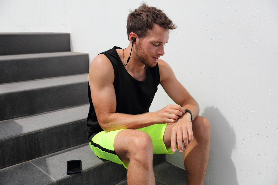 Smartwatch runner man checking progress on smart fitness sport watch during running break after hiit