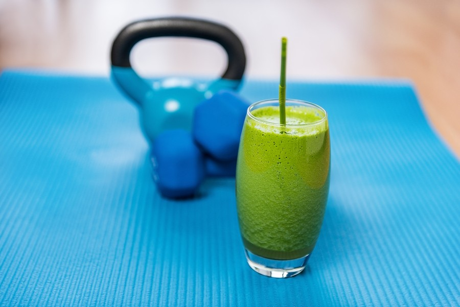 Weight loss healthy eating green vegetable smoothie with free weights kettlebells and exercise mat i